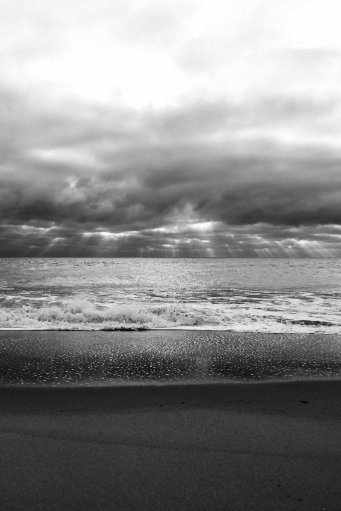 Rays of light shining through cloudy skies onto an angry ocean