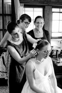 Bridesmaids helping a bride with her beautiful wedding dress