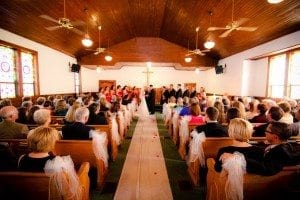 Man and woman getting married in front of a congregation of people