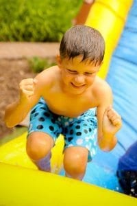 An excited child playing in water at a birthday party